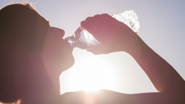 Young woman drinking water after high intensity training