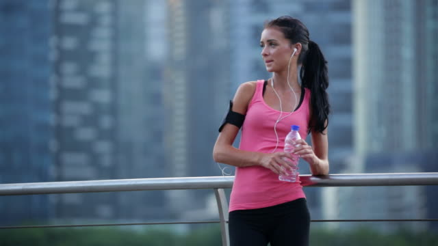 MS Young woman drinking water after working out.