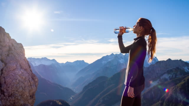 Young woman drinking water at the top of a mountain