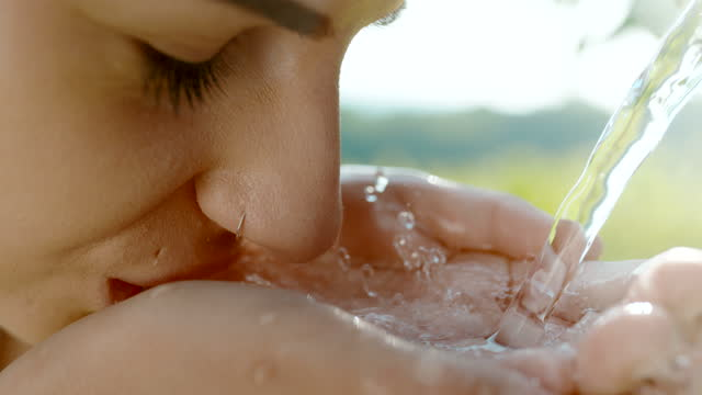 super slo mo young woman drinking water from cupped hands - pouring stock videos & royalty-free footage