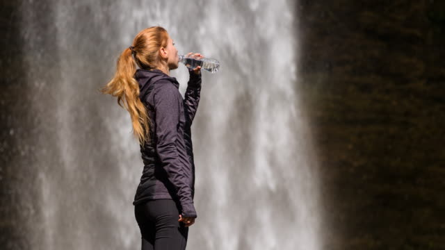 Young woman drinking water in front of a waterfall
