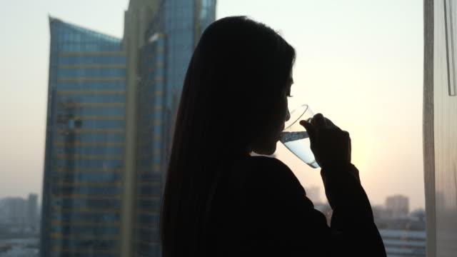 young woman drinking water in her room. - mineral stock videos & royalty-free footage