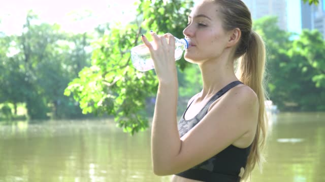 young woman drinking water in park - organized group stock videos & royalty-free footage