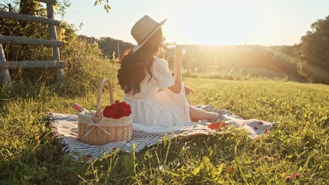 vídeos y material grabado en eventos de stock de slow motion mujer joven bebiendo vino en la naturaleza en el día soleado - picnic