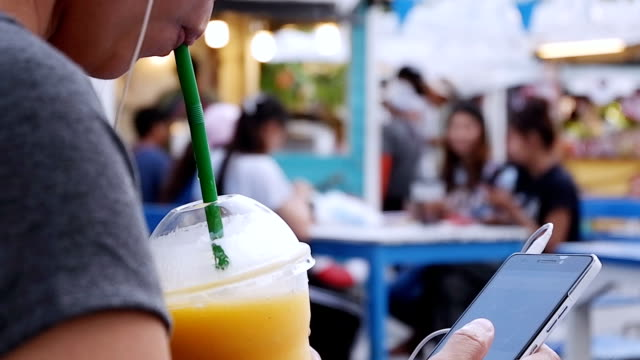 young woman drinking yellow mango smoothie on beach. closeup of female enjoying summer vacation. she is living healthy lifestyle outdoors smiling. - cold drink stock videos and b-roll footage