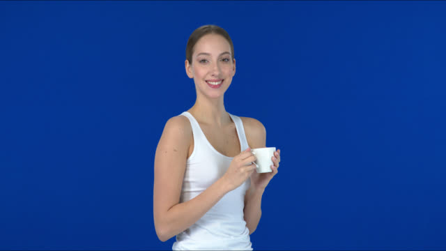 stockvideo's en b-roll-footage met de jonge vrouwendranken genieten van een kop koffie. - natuurlijk haar