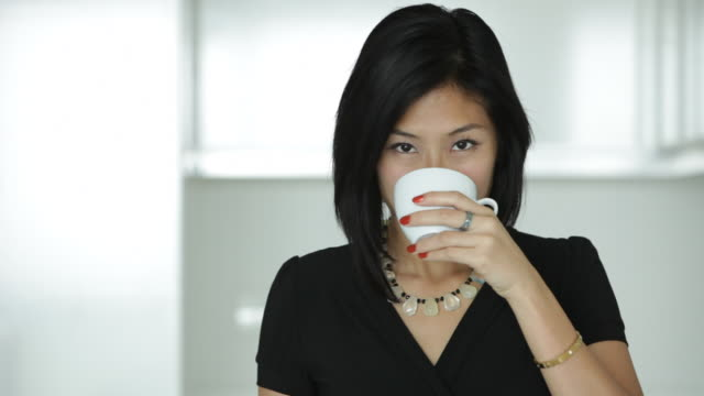 A young woman drinks from a white teacup, then laughs.
