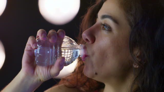 young woman drinks water from clear bottle while working out 4k - vesper stock stock videos & royalty-free footage