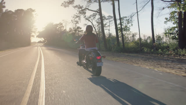 slo mo. young woman drives motorcycle into the sunlight on empty coastal highway. - riding stock videos & royalty-free footage