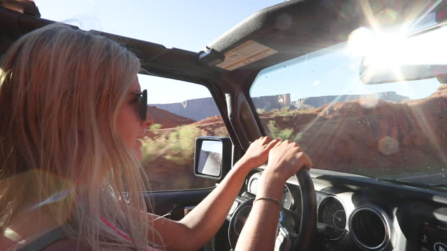 young woman drives vehicle on desert road - moab utah stock videos & royalty-free footage