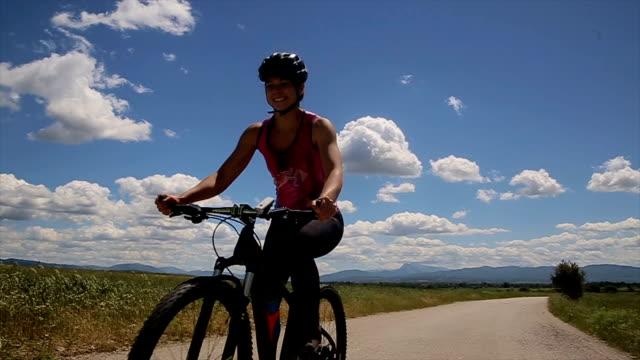 vídeos de stock, filmes e b-roll de jovem mulher dirigindo uma bicicleta, esportes, treinamento em incrível paisagem - sports training