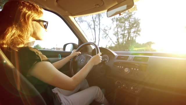Young woman driving at sunset