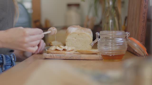 vídeos y material grabado en eventos de stock de cu young woman drizzling honey on fresh bread on kitchen counter - al horno