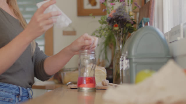 young woman drops ice cubes into a reusable water bottle full of red juice in the kitchen - bottle stock videos & royalty-free footage