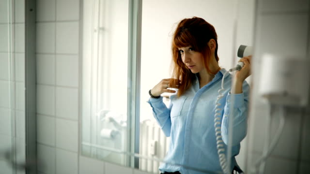 浴室で彼女の髪を乾燥若い女性 - 衣類乾燥機点の映像素材/bロール