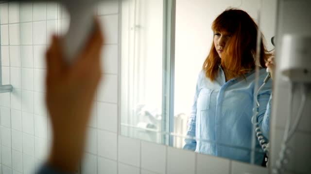 stockvideo's en b-roll-footage met jonge vrouw droogt haar haar in de badkamer - roodhoofd