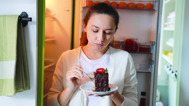 young woman eat appetizing cake using fork feeling pleasant - brown hair stock videos & royalty-free footage