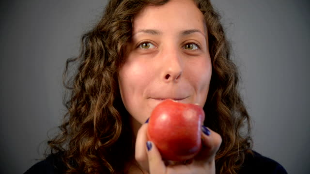 Young woman eat red apple.