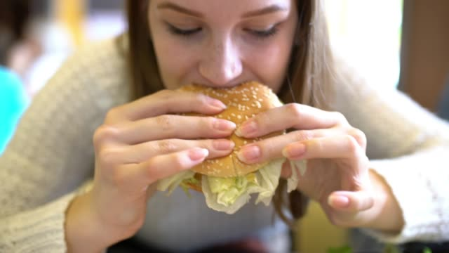 MS Young woman eating a hamburger in a restaurant