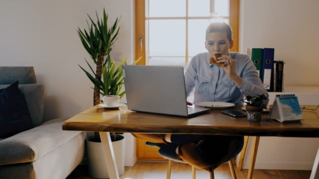 ds young woman eating a snack while working on a laptop from home - snack stock videos & royalty-free footage