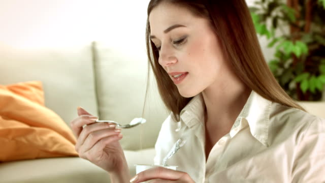 HD: Young Woman Eating A Yogurt