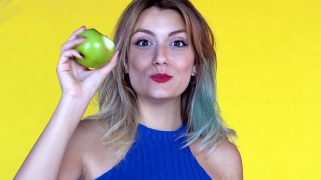 young woman eating an apple - mela video stock e b–roll