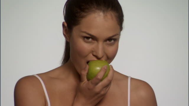 slo mo, cu, young woman eating apple in studio, portrait - see other clips from this shoot 125 stock videos and b-roll footage