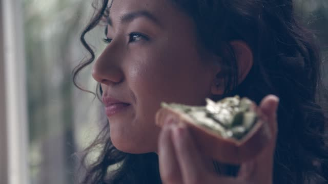 vidéos et rushes de ecu young woman eating avocado toast at home. - aliments et boissons