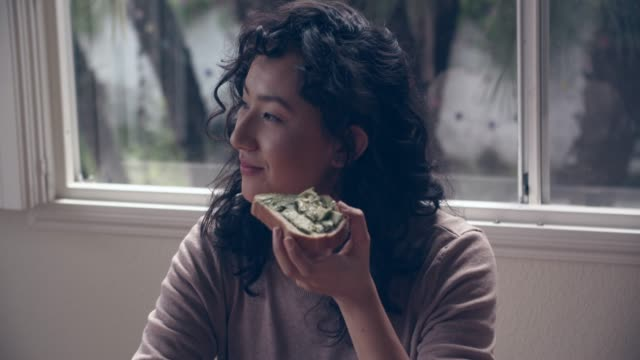 cu young woman eating avocado toast at home - eating bildbanksvideor och videomaterial från bakom kulisserna