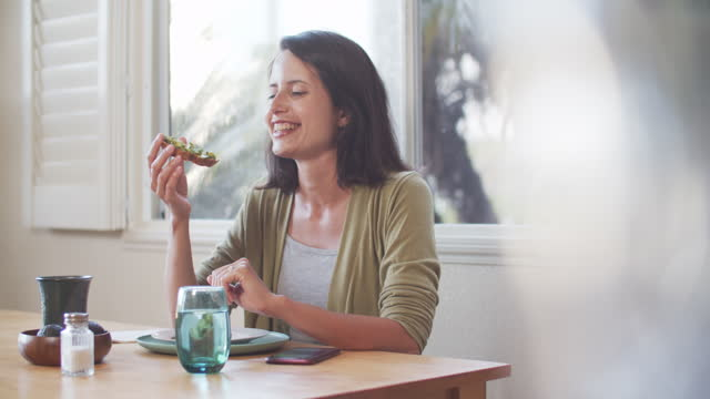 young woman eating avocado toast at home - young women stock videos & royalty-free footage