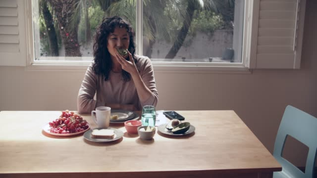ws young woman eating breakfast at home - kaffee getränk stock-videos und b-roll-filmmaterial