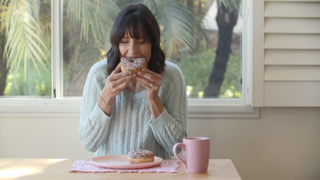 young woman eating breakfast at home - pink colour stock videos & royalty-free footage