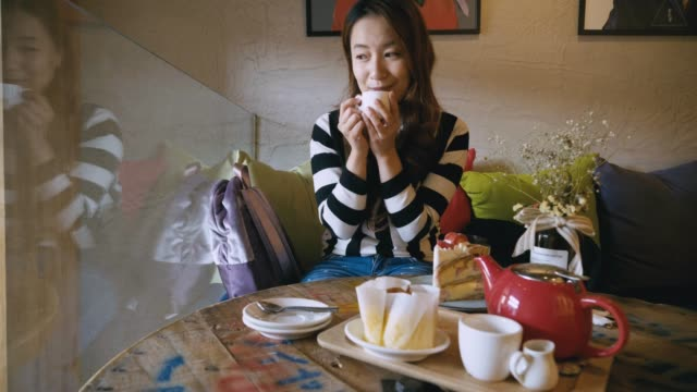 young woman eating cake to drink tea at coffee shop - coffee drink stock videos & royalty-free footage