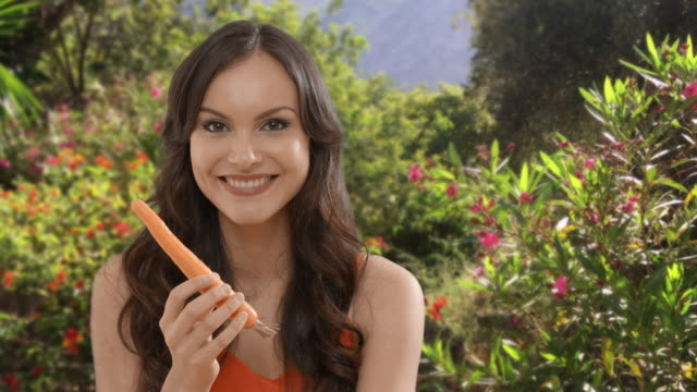 young woman eating carrot in garden - carrot stock-videos und b-roll-filmmaterial