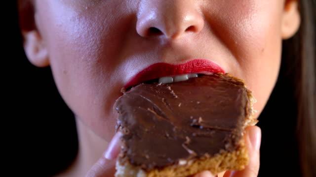 vídeos de stock e filmes b-roll de young woman eating chocolate cake - pasta