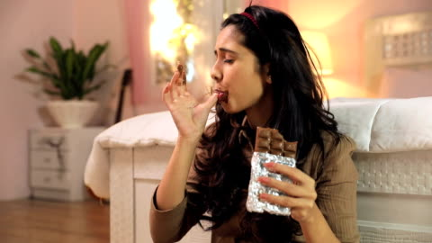 young woman eating chocolate, delhi, india - chocolate stock videos & royalty-free footage