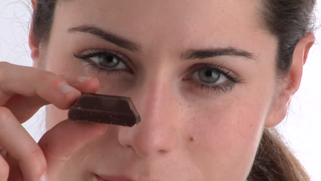 ECU, Young woman eating chocolate