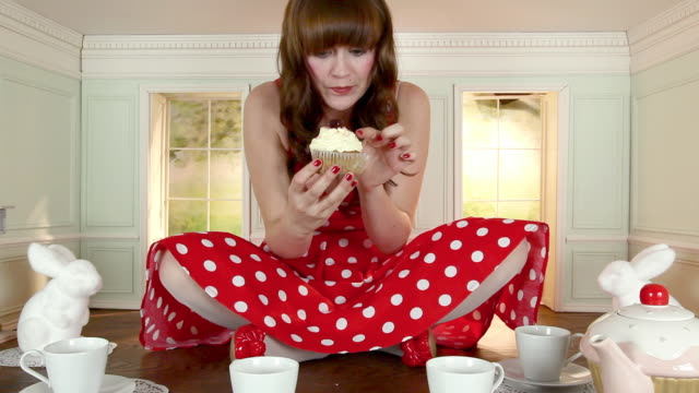 young woman eating cupcake in small house - tea party stock videos and b-roll footage