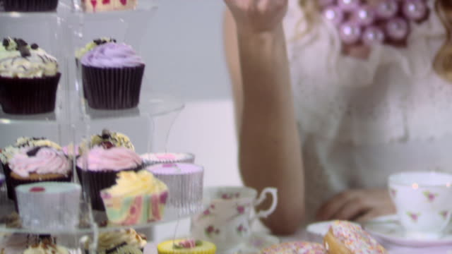young woman eating cupcake - tea party stock videos and b-roll footage