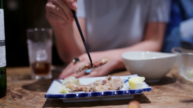日本の居酒屋で食べ物を食べる若い女性 - 居酒屋点の映像素材/bロール