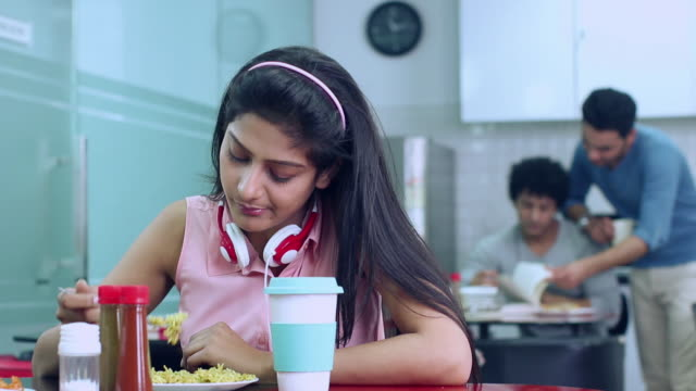 Young woman eating food in the cafeteria