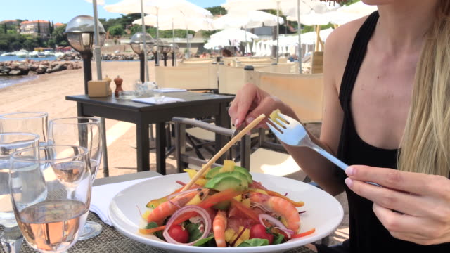 young woman eating fresh salad front of mediterranean sea - mediterranean food stock videos & royalty-free footage