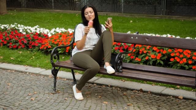 vídeos de stock, filmes e b-roll de jovem mulher comendo sorvete e brincar com o telefone - sentando