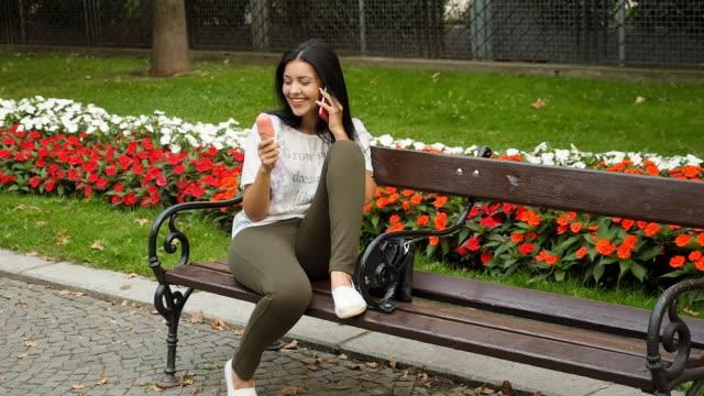 vídeos de stock, filmes e b-roll de jovem mulher comendo sorvete e falar ao telefone - sentando