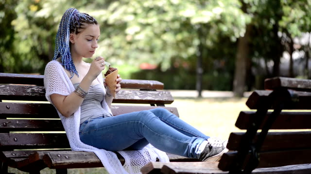 junge frau sitzen auf einer bank im park eis essen - joghurt stock-videos und b-roll-filmmaterial