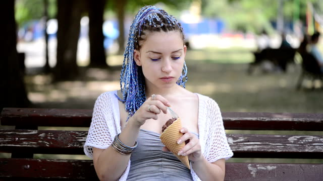 young woman eating ice cream sitting on a bench in the park - spoon stock videos & royalty-free footage