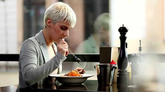 vídeos de stock e filmes b-roll de jovem mulher comer em um restaurante. - solidão
