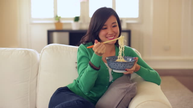 ms young woman eating noodles at home. - 麺点の映像素材/bロール