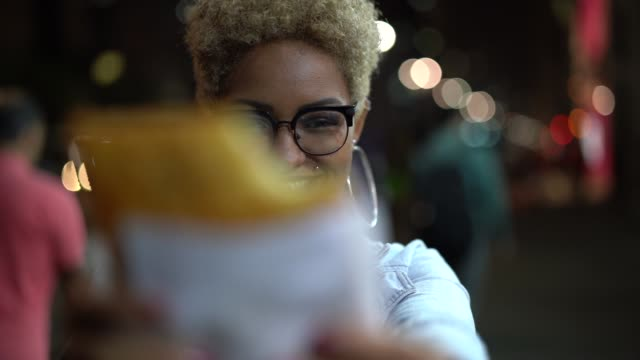 young woman eating pastel on the street after work - afro video stock e b–roll