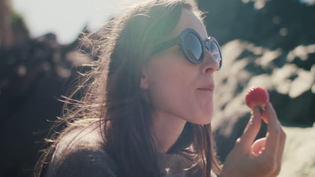 stockvideo's en b-roll-footage met young woman eating strawberry on rocky beach - gezonde voeding